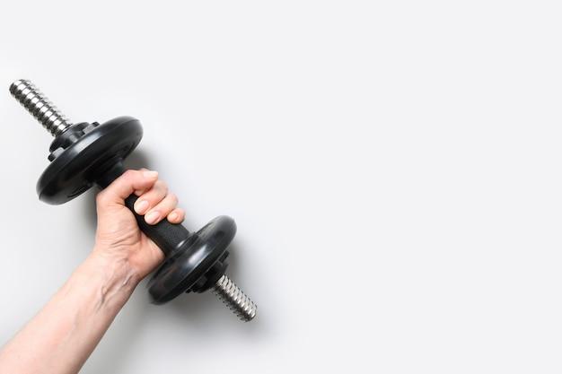Ręka z czarnym hantle na szarym tle. sprzęt do ćwiczeń sportowych.