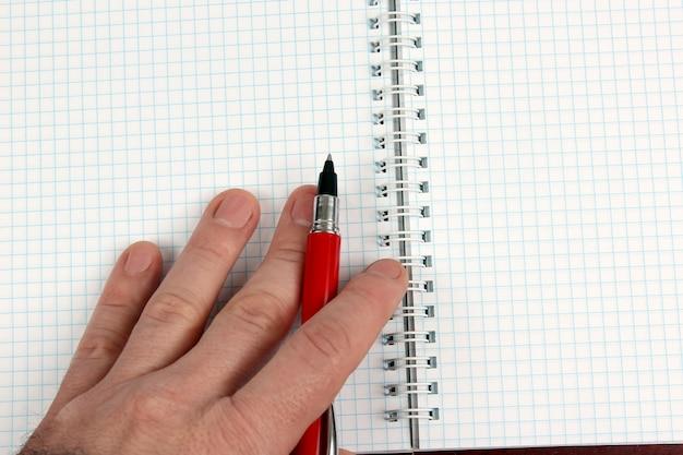Ręka z czerwonym długopisem przy zeszycie