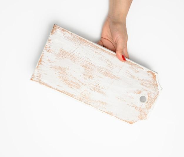 Ręka z czerwonym manicure trzyma pustą białą drewnianą prostokątną kuchnię z deską do krojenia