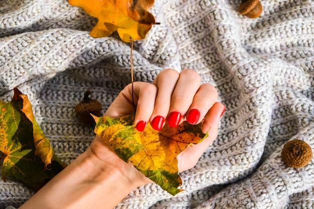 Ręka z czerwonymi paznokciami na swetrze jesień przytulne tło. kobiecy manicure. efektowny piękny manicure. manicure zimowy lub jesienny w kolorze czerwonym. modny lakier do paznokci w kolorze żelowym