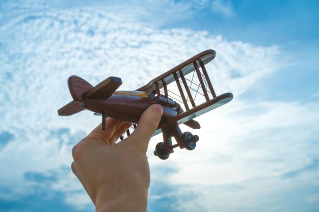 Ręka z drewnianym samolotem na tle błękitnego nieba