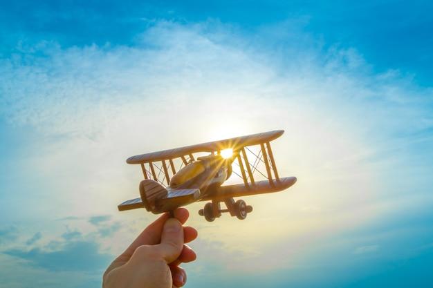 Ręka z drewnianym samolotem na tle zachodu słońca