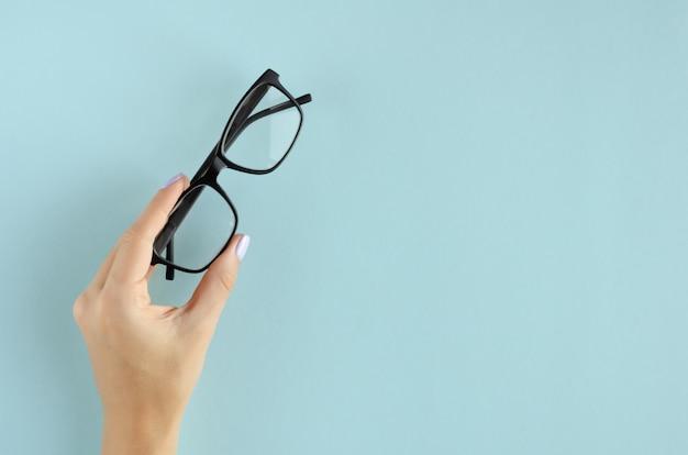 Ręka z eyeglasses składem na błękitnym tle.
