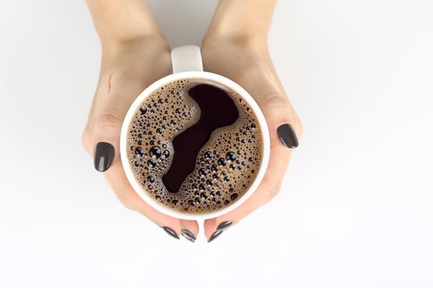 Ręka z filiżanką czarnej kawy na białym blacie