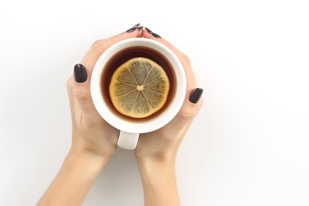 Ręka z filiżanką herbaty z cytryną na białym blacie