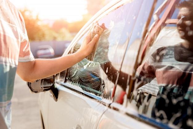 Ręka z gąbką czyści samochód