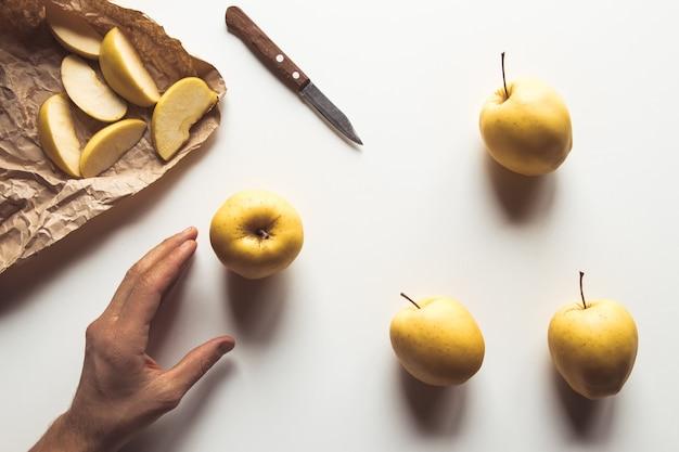 Ręka z jabłkiem z pięknym układem na białym tle. zdrowa żywność, produkty rolne, wegańskie