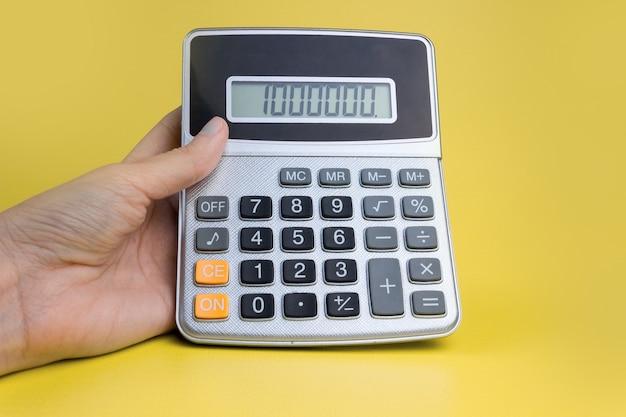Ręka z kalkulatorem na żółtym tle. pojęcie finansów, biznesu, pieniędzy, księgowości, oszczędności