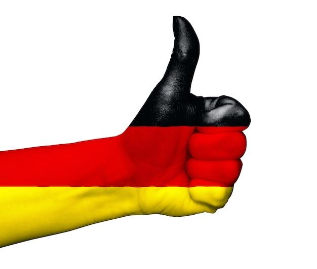Ręka z kciuk pomalowane w kolory flagi niemiec na białym tle