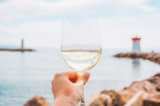 Ręka z kieliszkiem białego wina na morzu kamieni i tle latarni we francji