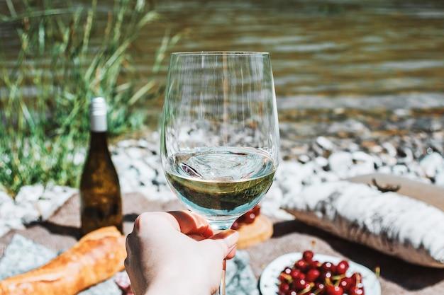 Ręka z kieliszkiem białego wina na wybrzeżu rzeki i piknikowym tle