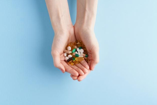 Ręka z kilkoma porozrzucanymi lekarstwami, pigułkami i tabletkami na niebieskim tle