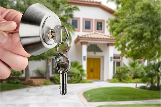 Ręka z kluczem do domu i zamkiem domu