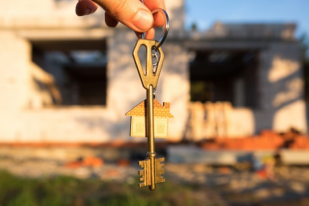 Ręka z kluczem do przyszłego domu na tle placu budowy i ścian