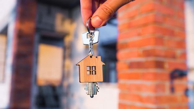 Ręka z kluczem do przyszłego domu na tle placu budowy