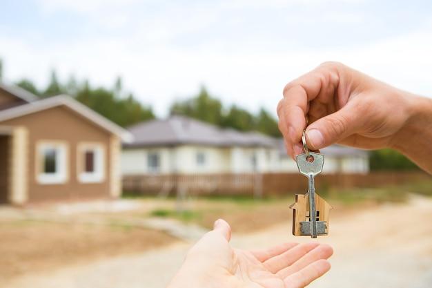 Ręka z kluczem i drewnianym domkiem na klucze