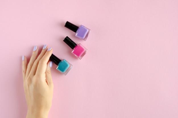 Ręka z kolorową kompozycją lakieru do paznokci na różowym tle.