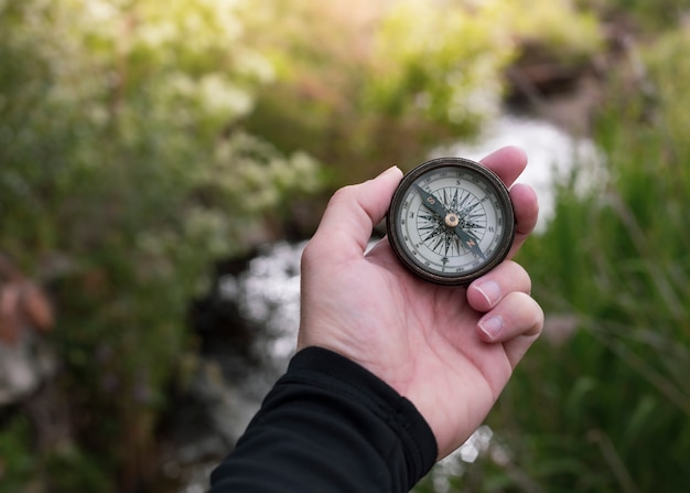 Ręka z kompasem na górskiej drodze do zachodu słońca niebo, pole zbóż lub pszenicy