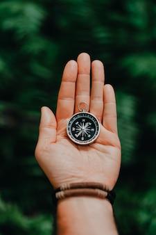 Ręka z kompasem na tle tropikalnej dżungli. koncepcja podróży pov.