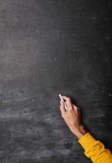 Ręka z kredą zamierza pisać na tablicy