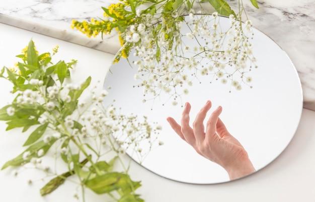 Ręka z kwiatami w lustrze