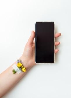 Ręka z kwiatem i telefonem na białym tle