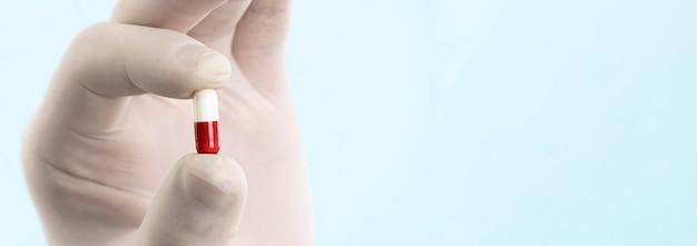Ręka z lateksową rękawicą trzyma pigułkę z miejsca na kopię