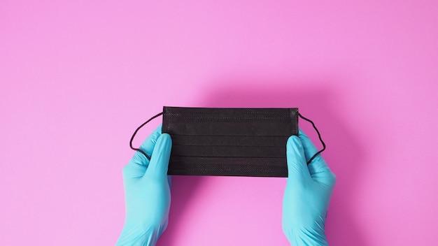 Ręka z lateksowymi rękawiczkami i trzymająca czarną maskę chroniącą przed infekcją wirusową. połóż na różowym tle.