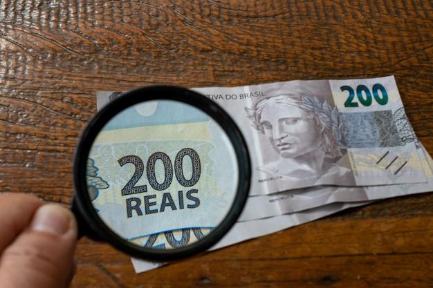 Ręka z lupą oglądając nowy brazylijski banknot na rustykalnym stole. dwieście reali.