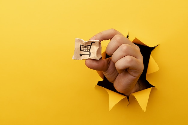 Ręka z małym pękniętym pudełkiem wysyłkowym przez żółty otwór na papier.
