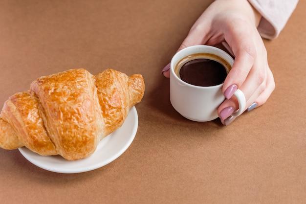 Ręka z manicure trzyma filiżankę kawy i jedzenie rogalika. śniadanie w stylu francuskim