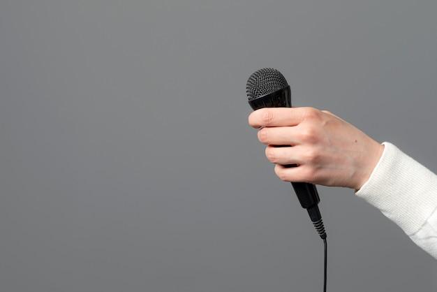 Ręka z mikrofonem na szarym tle, zbliżenie
