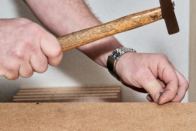 Ręka z młotkiem, młotkiem, młotkiem, gwoździem podczas montażu mebli