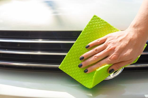 Ręka z myjką z mikrofibry do czyszczenia samochodu
