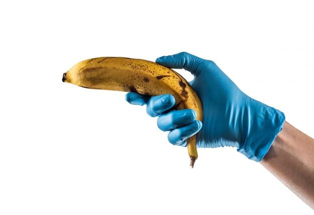 Ręka z niebieską rękawicą lateksową trzymająca banana