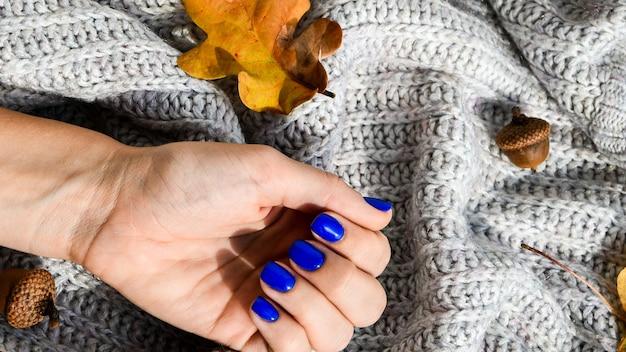 Ręka z niebieskimi gwoździami na sweter jesień przytulne tło. kobiecy manicure. efektowny piękny manicure. zimowy lub jesienny manicure w kolorze niebieskim. modny lakier do paznokci w kolorze żelowym