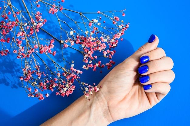 Ręka z niebieskimi gwoździami na tle suszonych kwiatów. kobiecy manicure. efektowny piękny manicure. zimowy lub jesienny manicure w kolorze niebieskim. modny lakier do paznokci w kolorze żelowym