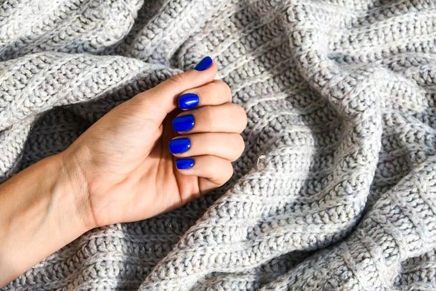 Ręka z niebieskimi gwoździami na tle swetra. kobiecy manicure. efektowny piękny manicure. pielęgnacja siebie i skóry.