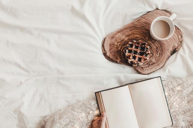 Ręka z notatnikiem blisko ciastka i gorącego napoju na stojaku na prześcieradle