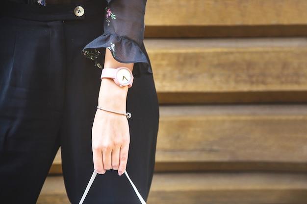Ręka z nowoczesnym zegarkiem, bransoletą i torbą na tle drewnianej ściany.