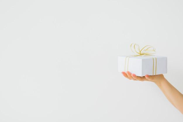 Ręka z obecnym pudełkiem w opakowaniu