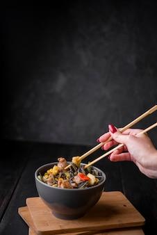 Ręka z pałeczkami mieszania w misce z makaronem