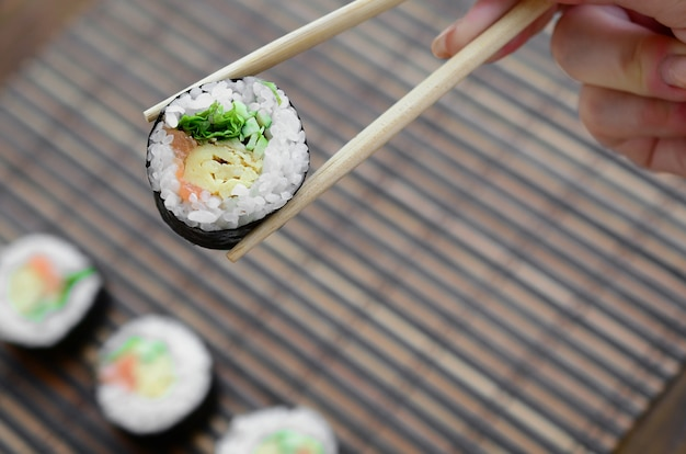 Ręka z pałeczkami trzyma rolkę sushi na bambusowej słomianej macie