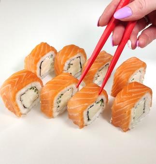 Ręka z pałeczkami zabiera ziemię. sushi na białej ścianie.