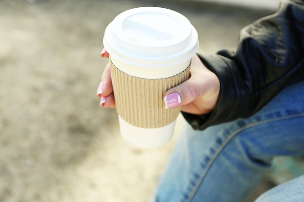 Ręka z papierową filiżanką kawy na zewnątrz, zbliżenie