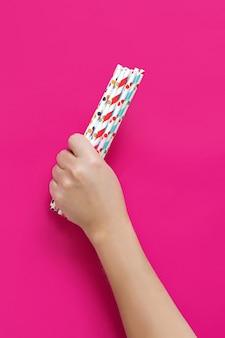 Ręka z papierowymi słomkami do picia na różowym tle z bliska. przyjazny dla środowiska i biodegradowalny