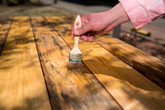 Ręka z pędzelkiem lakieruje stare deski drewniane