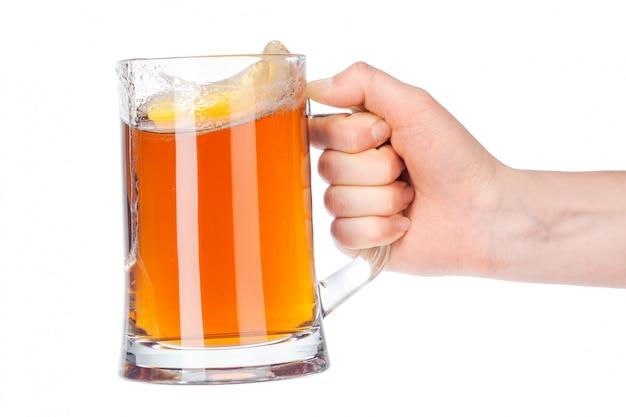 Ręka z pełnym piwnym szkłem odizolowywającym na bielu