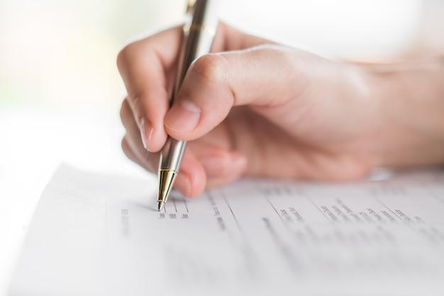 Ręka z piórem nad formularz wniosku.
