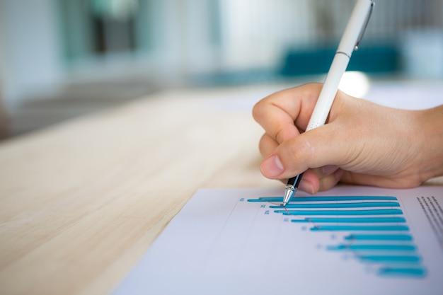 Ręka z piórem pisanie na papierze z wykresu słupkowego